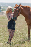 Girl in polka-dot dress with brown horse Royalty Free Stock Image