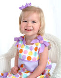 Girl in Polka Dot Dress on Chair Royalty Free Stock Photography