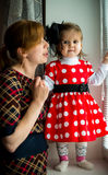 Girl in polka-dot dress and mother Stock Photography