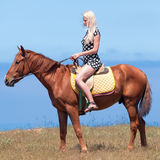 Girl in polka-dot dress rides on brown gelding. Horsewoman. Young blonde woman in polka-dot dress rides on brown gelding Royalty Free Stock Image