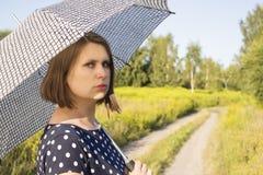 Girl in polka dot dress under the scorching sun Stock Photo