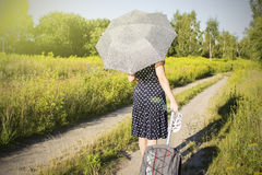 Girl in polka dot dress under the scorching sun walking on a forest road Stock Photography