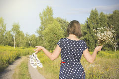 Girl in polka dot dress under the scorching sun walking on a forest road Stock Images