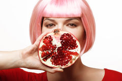 Girl with pomegranate. Pink hair. Royalty Free Stock Photos