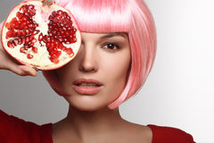 Girl with pomegranate. Pink hair. Stock Image