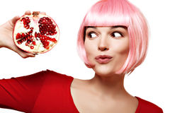 Girl with pomegranate. Pink hair. Makeup. Stock Photo