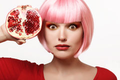 Girl with pomegranate. Pink hair. Makeup. Beautiful girl with pomegranate. Makeup. Ripe and juicy. Pink hair Stock Photo