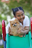 Girl and pomeranian dog in field Royalty Free Stock Photos