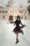 Girl in pompadour-style pompadour with a great haircut and a corset. Baroque and Rococo spirit. Girl in black cute Gothic dress jumping on the background of the Royalty Free Stock Photography