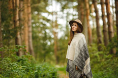 A girl in a poncho and a hat in forest Stock Photos