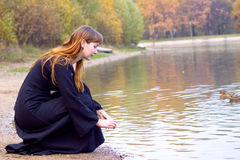 Girl, pond and ducks. Girl in black dress sitting near pond with ducks Stock Image