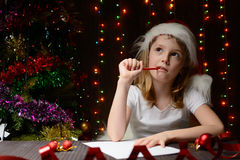 Girl pondered letter to Santa Claus Royalty Free Stock Images