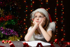 Girl pondered letter to Santa Claus Stock Image