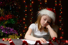 Girl pondered letter to Santa Claus Stock Photos