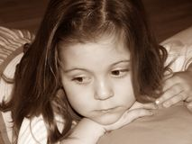 Girl Pondering. Sepia image of a little girl's face Stock Photo