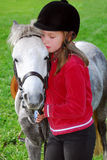 Girl and pony. Young girl with a white pony at countryside