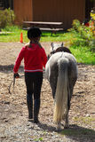 Girl and pony. Young girl leading her pony back to the stable Royalty Free Stock Photo