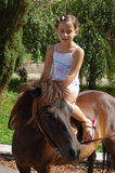 Girl on a pony. Little girl on a pony in the summer park Stock Photography