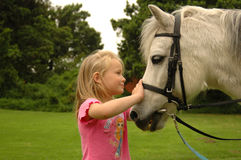 Girl with pony. A beautiful little white caucasian girl with long blond hair and happy smiling expression in her face together with her best friend, a white pony Stock Photography