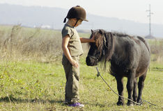 Girl with pony. Sweet little girl petting a cute pony outdoors Royalty Free Stock Photo