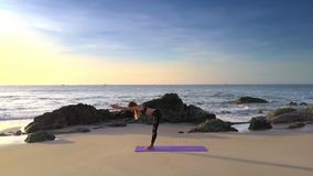 Girl with Ponytail Bends Body on Beach under Blue Sky. Fantastic panorama slim girl with ponytail in black leggings and top bends body in yoga on beach against stock video footage