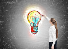 Girl with a ponytail drawing a light bulb Royalty Free Stock Photography