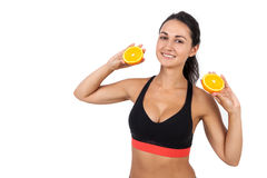 Girl with ponytail holding two halves of orange. Smiling girl with ponytail holding two halves of orange in her raised hands. Concept of natural food is good for stock photos