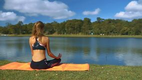 Girl with Ponytail Sits on Lake Bank Sky Reflects stock footage