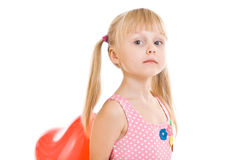 Girl with ponytails hides red balloon behind back Stock Photos