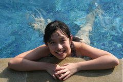 Girl at the pool. Happy girl playing alone in the swimming pool Stock Photos