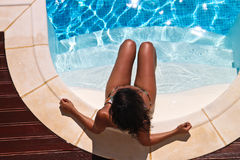 Girl at the pool. Brunet girl taking a sun bath at the pool Stock Images