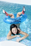 The girl in the pool. Smiling female at the edge of a swimming pool Stock Images