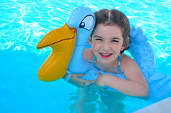 Happy girl with inflatable ring toy in water. Little girl with inflatable toy in blue water pool Royalty Free Stock Image