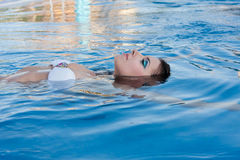 Girl in pool. Beautiful girl floating in the pool at the back Stock Photo