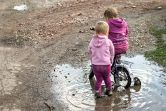 Girl in a pool. Little girls in a mud puddle Stock Image