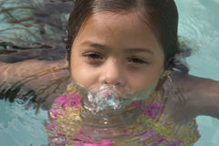 Girl in pool. Girl blowing bubbles in pool Stock Photo