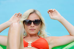 Girl in pool. A blonde girl in red bikini sun bathing on a green inflatable mattress in a swimming pool Royalty Free Stock Images