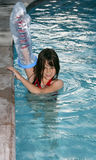 Girl in pool with cast. Young model with casted arm raised out of the pool stock images