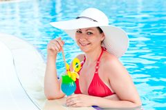 Girl in the pool with a cocktail Stock Image