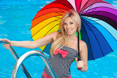 Girl by the pool with colored umbrella Stock Images