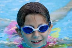 Girl in pool with goggles stock photography