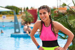 Girl at pool having a good time. Happy young woman in bikini playing and having a good time at water fun park pool, on a summer hot day Stock Image
