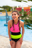 Girl at pool having a good time. Happy young woman in bikini playing and having a good time at water fun park pool, on a summer hot day Stock Images