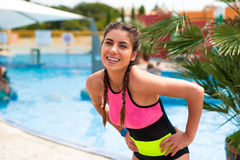 Girl at pool having a good time. Happy young woman in bikini playing and having a good time at water fun park pool, on a summer hot day Stock Photography