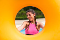 Girl at pool having a good time, playing with rubber float. Stock Images