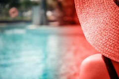 Girl at the pool. Living coral theme - color of the year 2019. Girl sitting at the pool edge Horizontal. Living coral theme - color of the year 2019 stock photo