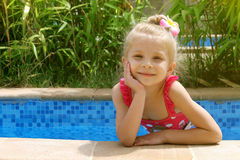 Girl in the pool with one hand near cheek Stock Photos