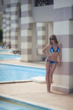 Girl by the pool. A pretty woman in bikini sunbathing at the beach Royalty Free Stock Images