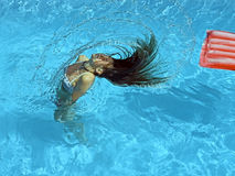 Girl in the pool. Girl shaking her hair in the pool Stock Image