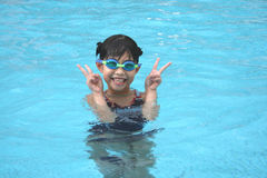 Girl in the pool showing victory sign. Girl in the swimming pool with hand showing victory sign Royalty Free Stock Image